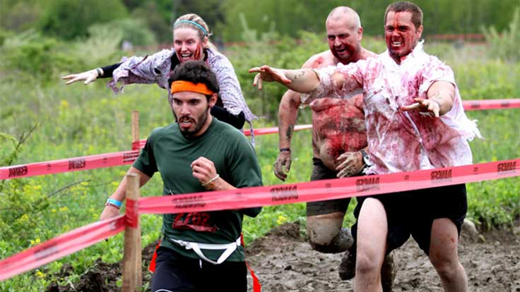 A man runs from three other people dressed as zombies on a muddy track