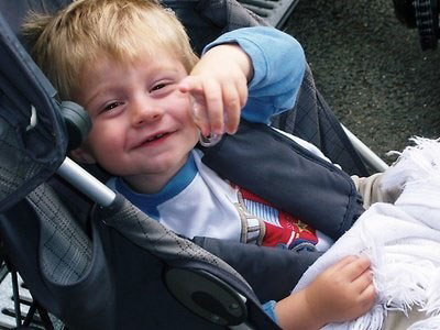 Cameron Brown sitting in his pushchair pointing and smiling at the camera