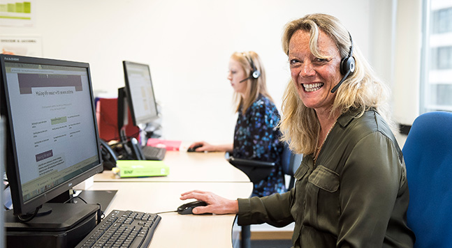 Nurse smiling wearing headset at a computer